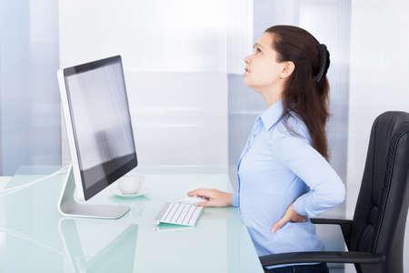 Portret van jonge zakenvrouw die aan rugpijn lijdt