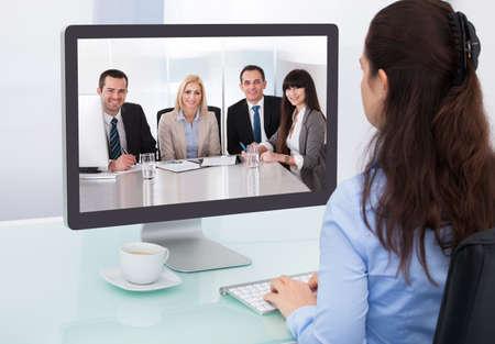 Zakenvrouw zittend aan een bureau kijken naar een online presentatie op de computer