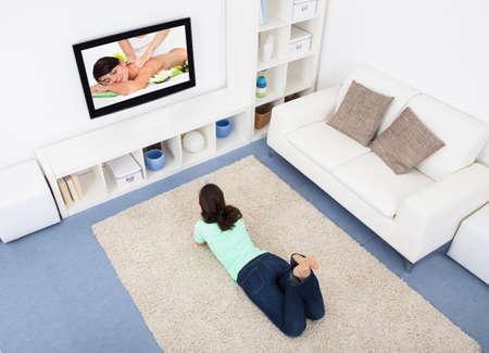 ver tv: Retrato de la mujer joven que miente en la alfombra que miran la televisión