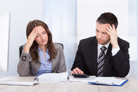 worried businessman: Worried Businessman And Woman Calculating Bills At Desk In Office Stock Photo