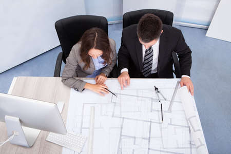 Two Architect Looking At Blue Print Discussing Together photo