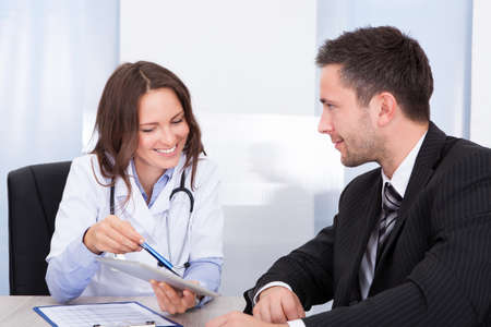 visit: Young Female Doctor Holding Clipboard Talking With Businessman