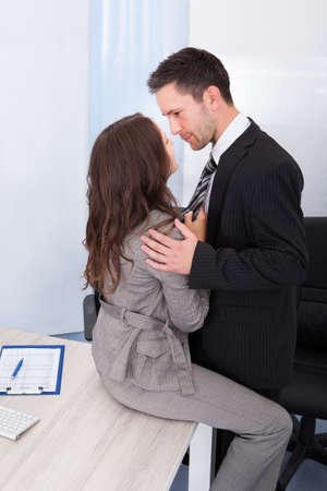 Naughty Businesswoman Holding Necktie Of Young Businessman photo