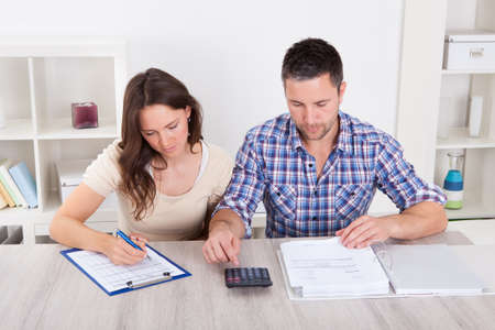 Portrait Of A Young Couple Calculating Finance At Desk Stock Photo - 24123050