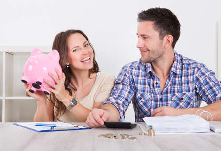 family budget: Young Man Looking At Woman Inserting Coin In Piggybank Stock Photo