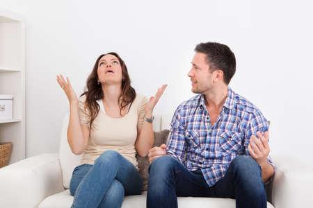 互いに口論してソファに座ってイライラのカップルの肖像画