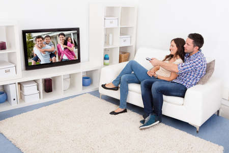 リビング ルームのテレビを見てソファの上で幸せな若いカップル