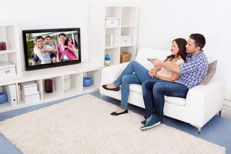 personas mirando: Feliz Pareja Joven En El Salón sentado en sofá viendo la televisión