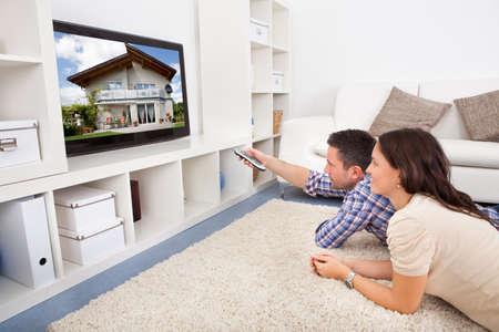 mann couch: Gl�ckliche junge Paar im Wohnzimmer sitzt auf Couch Fernsehen Lizenzfreie Bilder