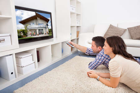tv room: Happy Young Couple In Livingroom Sitting On Couch Watching Television