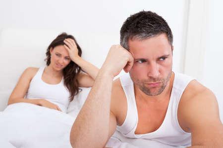 argument: Gefrustreerde Man Zittend Op Bed In De Voorkant Van Jonge Vrouw Stockfoto
