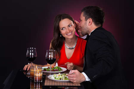 Man At Dining Table Whispering In Woman's Ear photo