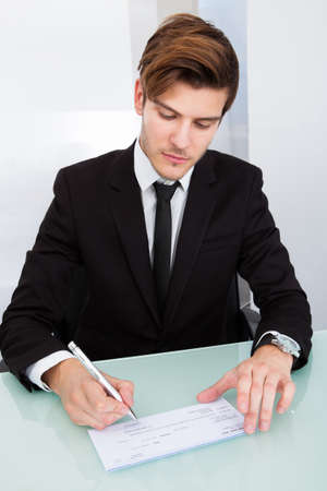 Young Businessman Filling Blank Cheque At Office Desk photo