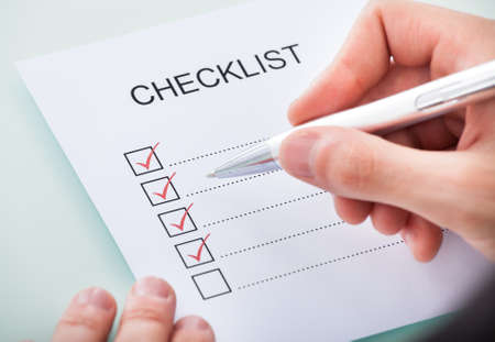 writing western: Close-up Of A Persons Hand Marking On Checklist With Pen Stock Photo