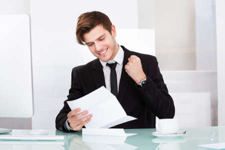 Successful Businessman Clenching His Fist Looking At Paper photo