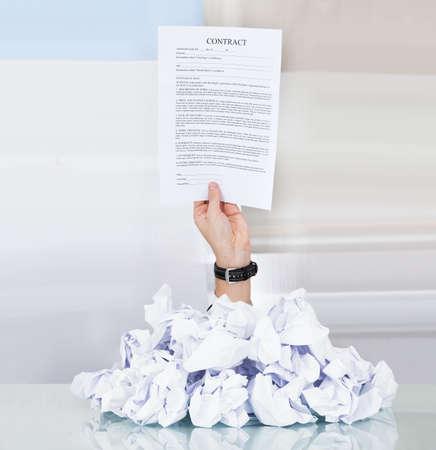 契約紙を開いてしわくちゃの紙の山の下の人