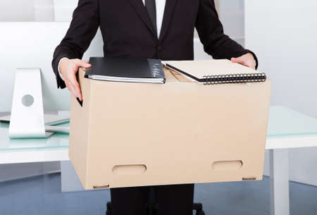 layoff: Close-up Of A Businessman Carrying Box At His Workplace