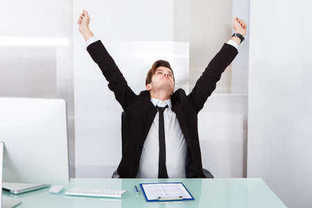 Portrait Of A Young Businessman Stretching At Office Desk photo