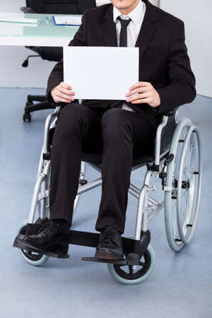 Close-up Of A Handicapped Businessman Holding Paper photo