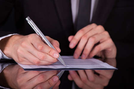 finance director: Close-up Of Businessman Writing On Paper With Pen