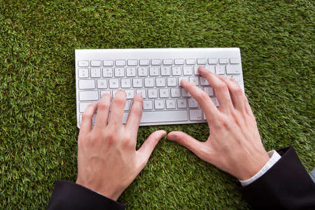 Close-up Of A Businessman Using Computer Keyboard Over Grass photo