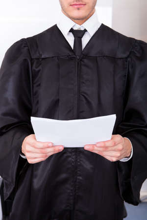 Close-up Of Male Judge In Robe Holding Judicial Documents