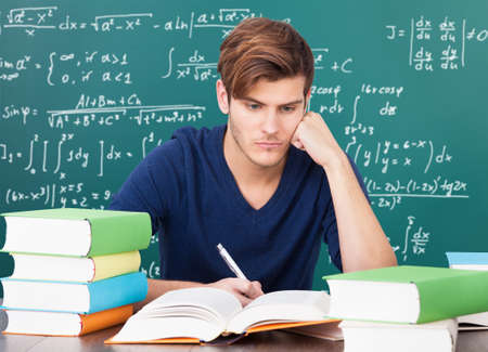 Serious Male Student Surrounded With Stack Of Books photo