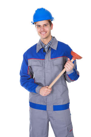 Happy Young Worker Holding Plunger On White Background photo