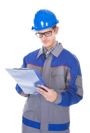 reviewer: Young Construction Reviewer Wearing Workwear And Hardhat Writing On Clipboard