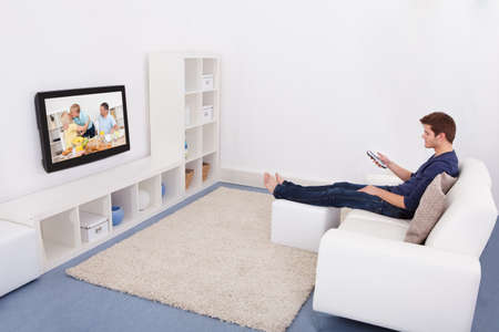 Young Man Sitting On Couch Watching Television photo