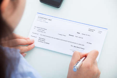 Close-up Of A Businesswoman Filling Blank Cheque At Desk photo
