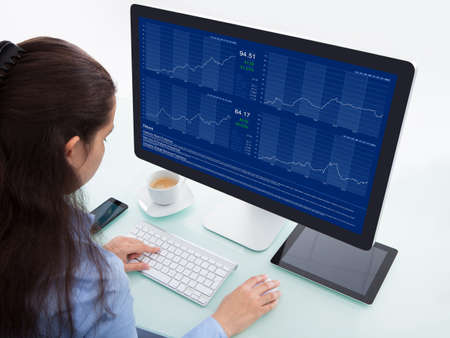 Portrait Of A Businesswoman At Desk Analyzing Graph On Computer photo