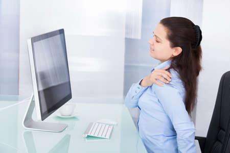 首の痛みに苦しんでいるコンピューターを使用して若い実業家 写真素材