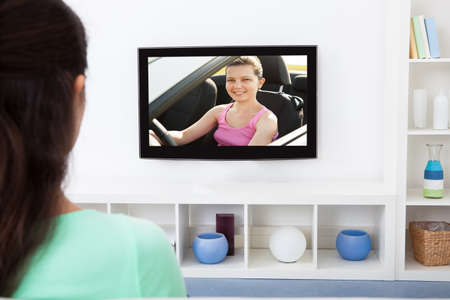 watch over: Close-up Of A Woman Watching Television At Home Stock Photo