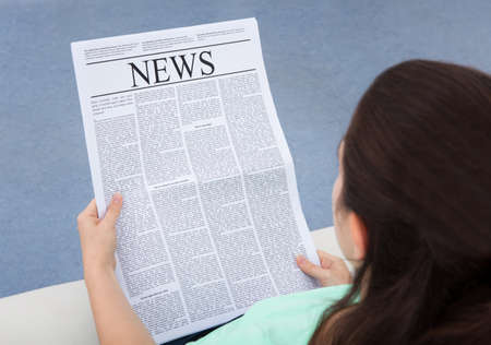 over shoulders: Rear View Of A Woman Sitting On Couch Reading Newspaper Stock Photo