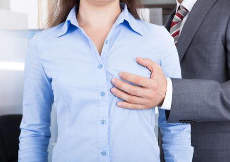 senos: Primer plano del hombre de negocios toca el pecho de la empresaria en oficina