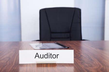 Naambord Met Auditor Titel Gehouden Op Bureau voor lege stoel Stockfoto