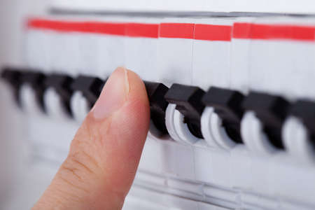 distribution board: Close-up Of Hand On Switch Of Distribution Board