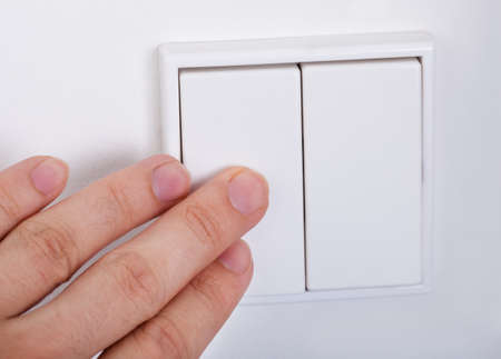 Close-up Of Hand Presses The Light Switch On The Wall photo