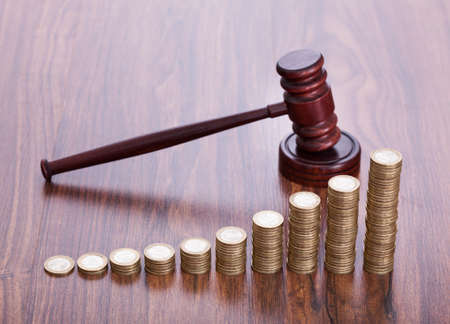financial official: Gavel With Pile Of Coins On Wooden Desk