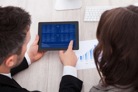 online trading: Rear View Of Young Businesspeople Analyzing Graph On Digital Table At Desk Stock Photo