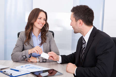 Happy Young Businessman And Businesswoman Exchanging Visiting Card At Office Desk photo