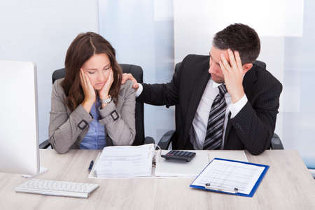 Worried Businessman And Woman Calculating Bills At Desk In Office photo