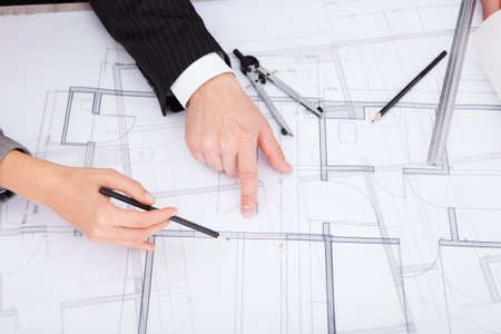 draftsman: Closeup Of A Persons Hand Pointing On Blue Print