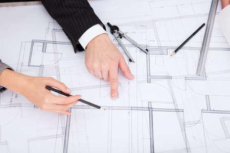 ingeniero civil: Primer De Señalando mano de una persona en Blue Print