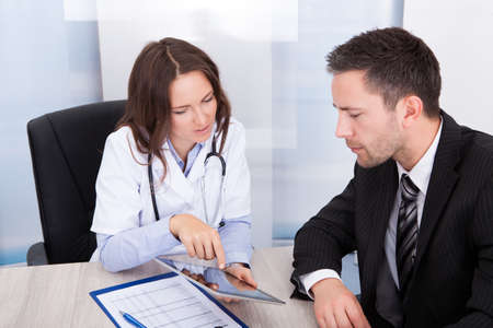 Young Female Doctor Showing Digital Tablet To Businessman Stock Photo