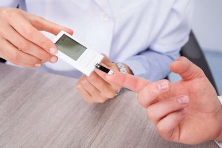 blood glucose level: Close-up Of Doctor Holding Patients Finger Checking Sugar Level Stock Photo
