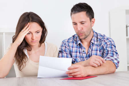 Portrait Of A Worried Young Couple Looking At Paper Stock Photo