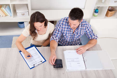 family budget: Portrait Of A Young Couple Calculating Finance At Desk