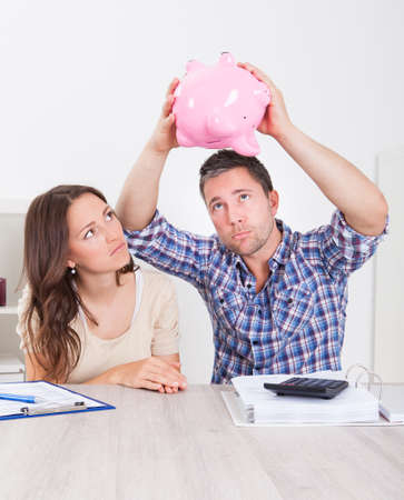 Woman Looking At Piggybank Raised By Young Man photo